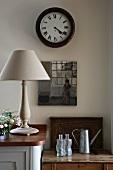 Schlichte Tischlampe auf Küchenunterschrank und antike Wanduhr über altem Holztisch