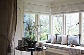 Comfortable window seat with a view and potted orchid on side table