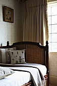 Traditional daybed with backrest in front of curtained window