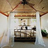 Hawaiian bedroom with mosquito netting around bed