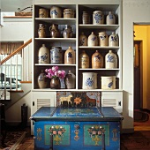 Shelving holding collection of 19th century stoneware with blue, hand-painted trunk in foreground
