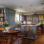 Offene Küche mit rundem Esstisch und Stühlen aus Holz und blauen Küchenschränken