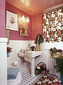 Bathroom with pink moiré wallpaper and floral curtain and rug