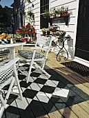 Terrace with table, chairs, plants and black and white chequered floor