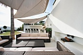 Contemporary outdoor sitting area beneath sunshade