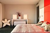 Designer Schlafzimmer mit rotem Bettkopfteil und Sessel in Blütenform neben Wandtisch