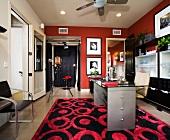 Wohnliches Photostudio - moderner Arbeitsraum mit Tisch auf gemustertem Teppich mit kräftigen Farben