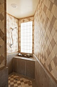Bathroom tiles on walls and floor in various shades of brown laid diagonally