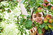 Smiling girl playing in fruit tree