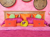 Pink and orange throw pillows on bed
