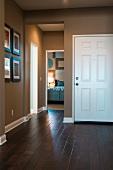 Eingangsdiele mit dunklem Holzparkett zu elegant braunbeiger Wand und offene Tür zum Schlafzimmer
