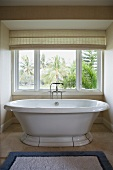 Modern bathtub with detachable shower head in front of window