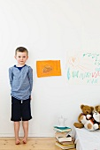 Boy with drawings on bedroom wall