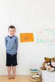 Junge steht an der Wand mit Zeichnungen