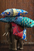 Stack of colourful cushions on back of wooden elephant figure in front of bamboo curtain