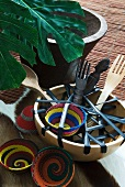 Wooden salad servers in bowl and colourful, African-style dishes on floor next to potted plant