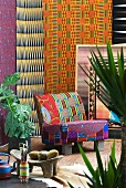 African style - colourful patterned chair in front of bright wall hangings surrounded by tropical potted plants