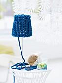Einfache Tischlampe, aufgepeppt mit grob gestricktem, blauem Lampenschirm und dekorativ drapiertem Garnende