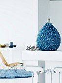 Pear-shaped bottle artistically encased in knitted, mottled blue yarn on kitchen counter