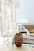 Dramatic, translucent capiz shell curtain above small, plexiglass table and basketwork vase; bed with simple bedspread in background
