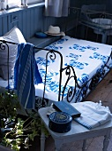 Metal bed with a bedspread decorated with a blue and white pattern