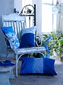 Blue and white decorative pillows on a wooden chair