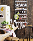 Metal rack of hooks for crockery, stool, table and fridge in rustic kitchen with wooden wall