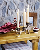 Artificial antler candelabra on wooden table top in front of stone-effect panel