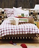 Bed with gingham flannel bed linen against wall clad in animal-skin patchwork and wood