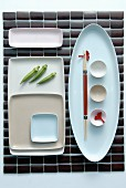 A place mat and a Japanese place setting with assorted dishes arranged geometrically