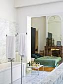 Marble bathroom with open doorway leading to bedroom