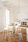 Spacious living room - kitchen in Mediterranean style -- dining table and chairs with rush wickerwork