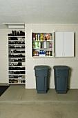 Grey plastic bins below open wall-mounted cupboard and shoe rack in utility room
