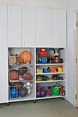 Fitted cupboards and shelves holding toys and sports equipment