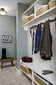 Cloakroom with storage baskets on shelves against grey-painted walls