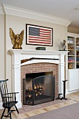 Fireplace with white-painted mantelpiece below American flag on wall of country house interior