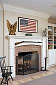Kamin mit weiss lackiertem Holzsims und amerikanische Flagge an Wand im Wohnraum eines Landhauses