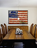 Dark wood dining table and rush-back chairs in front of painting of American flag on wall