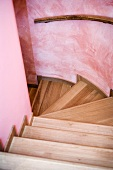 Wooden stair treads and handrail on curved, pink wall