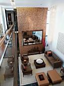 Blick von Galerie auf elegante Wohnzimmereinrichtung mit brauner Polstermöbelgarnitur und raumhoher Trennwand