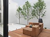 Zeitgenössisch gestylter Innenhof mit Rattanmöbeln auf Holzdeck und Baumreihe vor weisser Wand