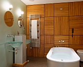 Free-standing bathtub in front of wood-panelled wall in designer bathroom