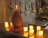 Glass tea light holders with lit candles next to cone-shaped candle on kitchen surface