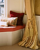 Cushions on window seat integrated into window niche next to curtain gathered with tasselled cord