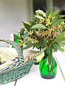 Vase of eucalyptus buds on white table next to basket of linen napkins
