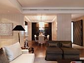 Moderner, offener Wohnraum mit Wohnzimmer in Naturfarben und dem Essbereich im Hintergrund