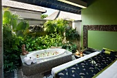 Spa room with massage table and sunken bath tub