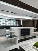Minimalistischer, offener Wohnraum mit einem zentralen Platz für das Fernsehgerät
