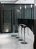 Moderne Küchentheke in Schwarz mit verchromten Barstühlen auf weißem Marmorboden
