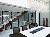 Modern dining room with beaded crystal chandelier and staircase